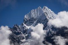 Picco sopra le nuvole, catena montuosa del montain di Thamserku dell'Himalaya immagini stock