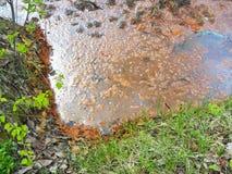 Piccola acqua di fiume inquinante tramite ruggine e rifiuti solidi Acque luride in natura Catastrofe ecologica immagini stock libere da diritti