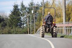 Piccola attrezzatura dell'azienda agricola sulla strada pubblica Immagine Stock