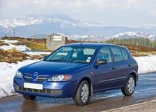 Piccola automobile blu in un paesaggio nevoso. Fotografia Stock Libera da Diritti