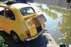 Piccola automobile italiana dell'annata con la valigia di vimini Immagine Stock