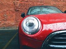 piccola automobile rossa su un fondo di un muro di mattoni Fotografia Stock Libera da Diritti