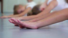 Piccola ballerina del primo piano che allunga sul pavimento che pratica nel movimento lento della scuola di balletto stock footage