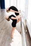 Piccola ballerina sveglia e suo l'insegnante che allungano nello studio di ballo Immagine Stock