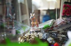 Piccola bambola di legno dei cervi decorata in un gabinetto di vetro che visualizza il condimento dei gioielli immagini stock