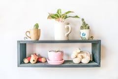 Piccola bambola e piccola pianta nella decorazione del vaso sulla struttura di legno su fondo bianco Fotografia Stock