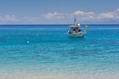 Piccola barca nelle acque blu del mare ionico immagine stock libera da diritti