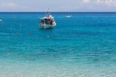 Piccola barca nelle acque blu del mare ionico fotografie stock libere da diritti