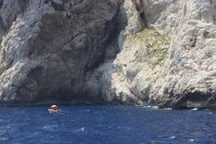 Piccola barca, oceano blu e spiaggia rocciosa Fotografia Stock