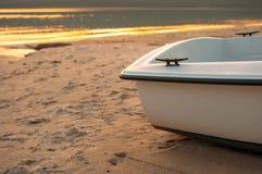 Piccola barca sulla spiaggia con il mare al tramonto Fotografia Stock
