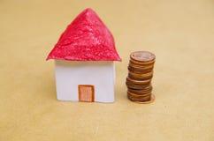 Piccola bella casa con le monete impilate davanti alla finzione di modello dell'alloggio: prezzi della casa, acquisto di una casa Immagine Stock Libera da Diritti