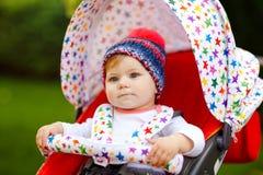 Piccola bella neonata in buona salute sveglia con il cappello caldo blu che si siede nella mamma della carrozzina o del passeggia fotografie stock libere da diritti