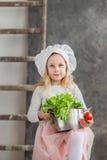 Piccola bella ragazza che giudica un vaso pieno delle verdure Alimento sano Piccola casalinga del raccolto fotografia stock libera da diritti