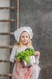Piccola bella ragazza che giudica un vaso pieno delle verdure Alimento sano Piccola casalinga del raccolto immagine stock