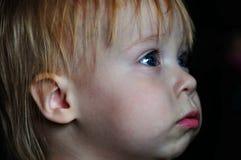 Piccola bella ragazza che guarda TV a casa fotografia stock