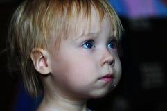 Piccola bella ragazza che guarda TV a casa fotografie stock