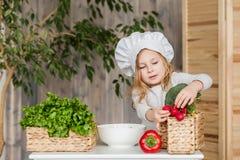 Piccola bella ragazza che produce insalata di verdure nella cucina Alimento sano Piccola casalinga fotografia stock