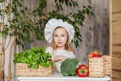 Piccola bella ragazza che produce insalata di verdure nella cucina Alimento sano Piccola casalinga immagine stock libera da diritti