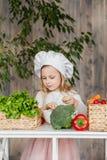 Piccola bella ragazza che produce insalata di verdure nella cucina Alimento sano Piccola casalinga fotografie stock libere da diritti