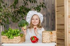 Piccola bella ragazza che produce insalata di verdure nella cucina Alimento sano Piccola casalinga immagini stock
