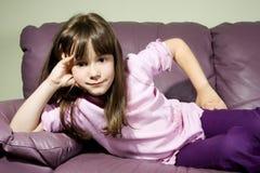 Piccola bella ragazza sorridente che propone sul sofà Immagine Stock