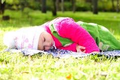 Piccola bella ragazza sull'erba verde entro l'autunno Immagini Stock