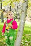 Piccola bella ragazza sull'erba verde entro l'autunno Fotografie Stock
