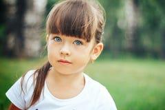 Piccola bella ragazza sveglia che esamina gli occhi azzurri della macchina fotografica Fotografia Stock