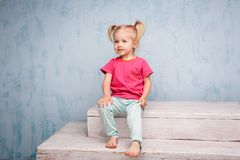 Piccola bionda favorita divertente del bambino della ragazza con le code di cavallo di un taglio di capelli due su lei seduta cap immagine stock