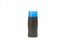 Piccola bottiglia in bianco nera con il cappuccio blu isolato su fondo bianco Fotografia Stock Libera da Diritti