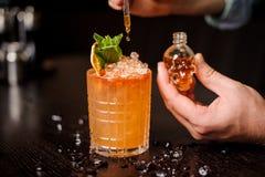 Piccola bottiglia a forma di cranio, cocktail arancio e mano dei baristi Immagini Stock Libere da Diritti