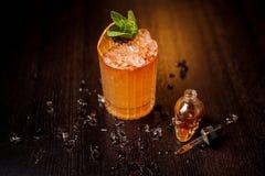 Piccola bottiglia a forma di cranio e cocktail arancio Fotografie Stock