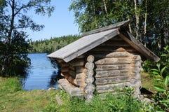 Piccola cabina di legno sulla banca del lago Fotografia Stock