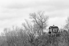 Piccola capanna modesta sopra un'alta collina circondata entro l'inverno nudo Fotografia Stock