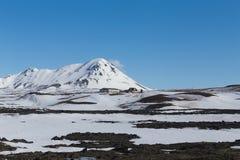 Piccola capanna sopra l'alta collina nella stagione invernale con il chiaro fondo del cielo blu, Islanda Immagine Stock