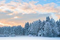 Piccola cappella di legno in foresta gelida isolata dalla neve sotto il cielo di alba Fotografia Stock Libera da Diritti