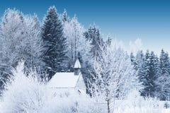 Piccola cappella di legno innevata nella foresta gelida di inverno Fotografia Stock