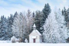 Piccola cappella di legno sulla radura gelida isolata dalla neve in foresta congelata nevosa Fotografie Stock