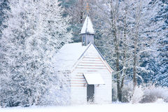 Piccola cappella legnosa in foresta nevosa congelata Immagini Stock
