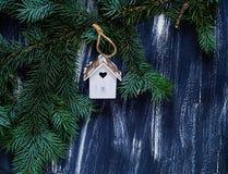 Piccola casa bianca con un cuore su un fondo di legno blu dell'albero di abete del ramo, spazio libero dell'elemento decorativo p Immagini Stock