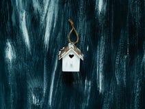 Piccola casa bianca con un cuore su un fondo di legno blu, spazio libero dell'elemento decorativo per testo Immagine Stock Libera da Diritti