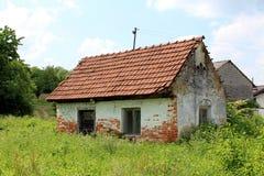 Piccola casa con mattoni a vista rovinata abbandonata circondata con erba non tagliata alta Immagine Stock