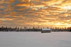 Piccola casa del granaio coperta di neve sotto i cieli drammatici Fotografia Stock Libera da Diritti