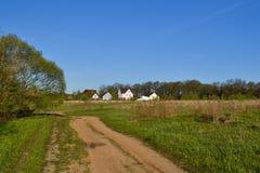 Piccola casa della famiglia sul campo verde con cielo blu Fotografie Stock