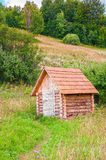 Piccola casa di ceppo di legno nel prato della foresta della montagna Fotografia Stock Libera da Diritti