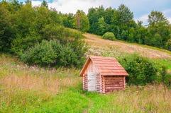 Piccola casa di ceppo di legno nel prato della foresta della montagna immagine stock libera da diritti