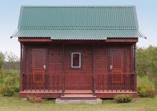 Piccola casa di legno sotto il tetto verde del metallo Fotografia Stock Libera da Diritti