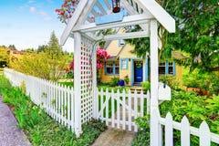Piccola casa gialla esteriore con la chiusura bianca Fotografia Stock Libera da Diritti