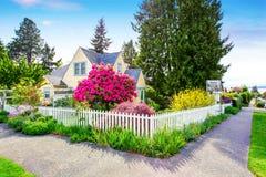 Piccola casa gialla esteriore con la chiusura bianca Fotografie Stock