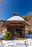 Piccola casa giapponese tradizionale del tetto ricoperto di paglia nel villaggio tradizionale di Iyashino-Sato Nenba coperto da n fotografie stock